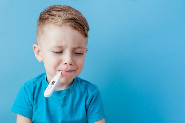 Krankes kleines kind mit einem thermomether, das die höhe seines fiebers misst und in die kamera schaut