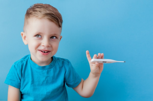 Krankes kleines kind mit einem thermomether, das die höhe seines fiebers misst