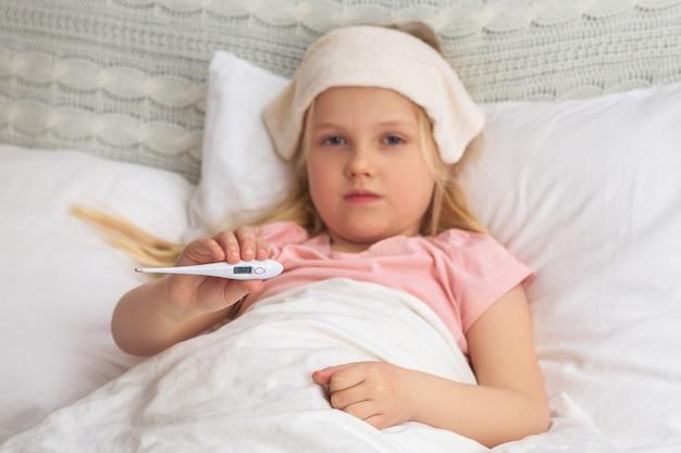 Krankes kleines kindermädchen, das im bett mit thermometer liegt.