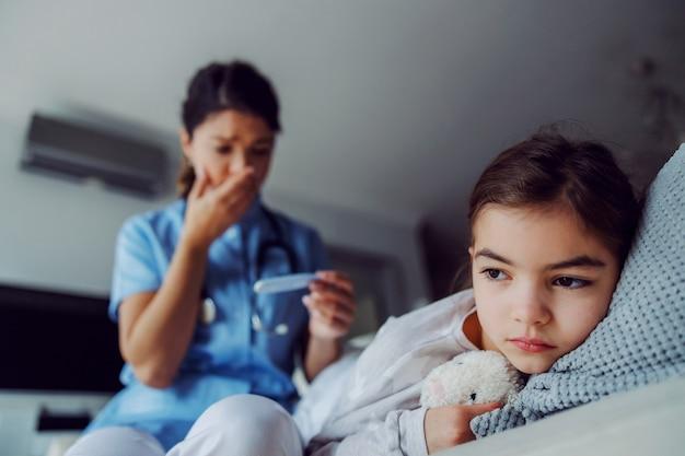 Krankes kleines mädchen, das auf dem bett im krankenhaus und geschockte krankenschwester liegt, schaut auf thermometer