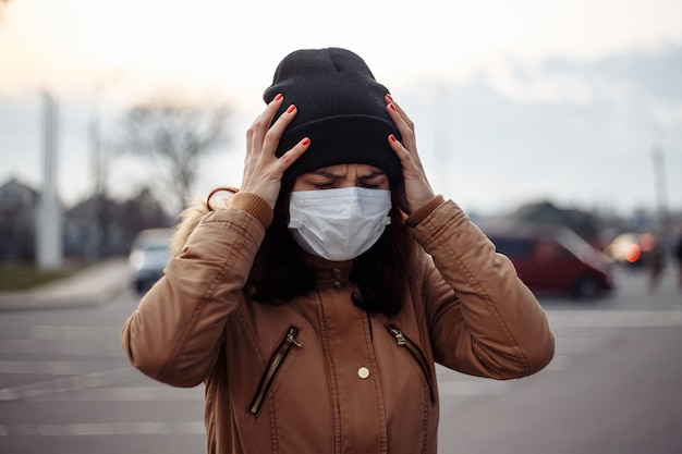 Krankes krankes mädchen trägt medizinische maske ängstliche frau in maske, die unter hitze leidet, kopfschmerzen kämpft auf der straße, fühlt sich schlecht. person braucht hilfe. virus, chinesisches pandemie-coronavirus, panikkonzept.