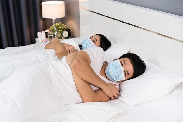 Krankes paar, das sich auf dem bett kalt fühlt und eine medizinische maske zum schutz der coronavirus-pandemie trägt