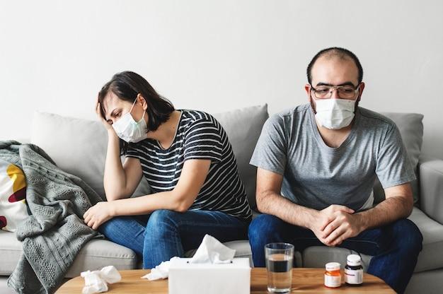 Krankes paar, das zusammen auf dem sofa sitzt