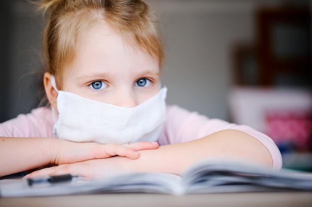 Krankes schulmädchen in der medizinischen maske und in den kopfhörern, die zu hause mit digitalem tablet studieren und schulhausaufgaben machen.