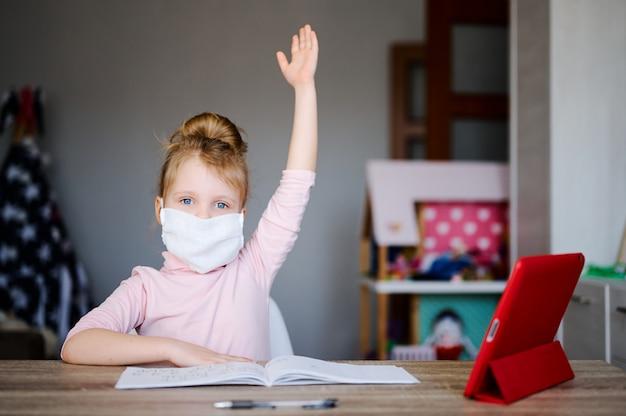 Krankes schulmädchen in medizinischer maske, das zu hause mit digitalem tablet lernt und hausaufgaben macht, hob die hände.