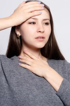 Krankheit, gesundheitswesen, menschen, medizinkonzept - halsschmerzen. nahaufnahme der kranken frau mit halsschmerzen, die sich schlecht fühlt und unter schmerzhaftem schlucken leidet. schönes mädchen, das den hals mit der hand berührt