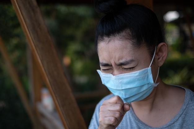Krankheit junge asiatische frau, die eine maske trägt