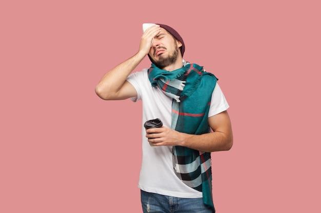 Krankheit moderner bärtiger junger hipster-mann in weißem hemd, hut und schal, der mit der hand seinen kopf berührt, starke kopfschmerzen hat und heißen tee in der tasse hält. innen, isoliert, studioaufnahme, rosa hintergrund