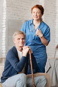 Krankheit vorbeugen. erfreute charismatisch motivierte frau, die eine konsultation für einen älteren patienten durchführt, ihn besucht und professionelle ausrüstung zur untersuchung verwendet