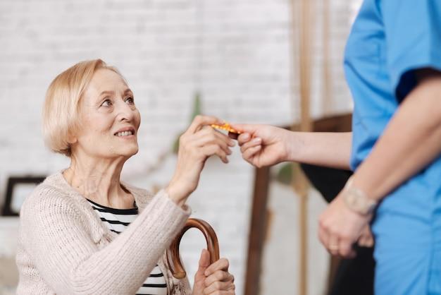 Krankheit vorbeugen. fleißige, kluge alte dame, die eine packung vitamine nimmt, die ihr arzt verschreibt, nachdem er ihr von den symptomen erzählt hat, die sie hat