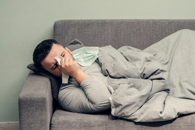 Krankheit. zu hause jubeln. ein junger mann ist krank, wird zu hause behandelt. schlägt ihre nase in eine serviette, laufende nase. infektion, epidemie, bazillus-träger.