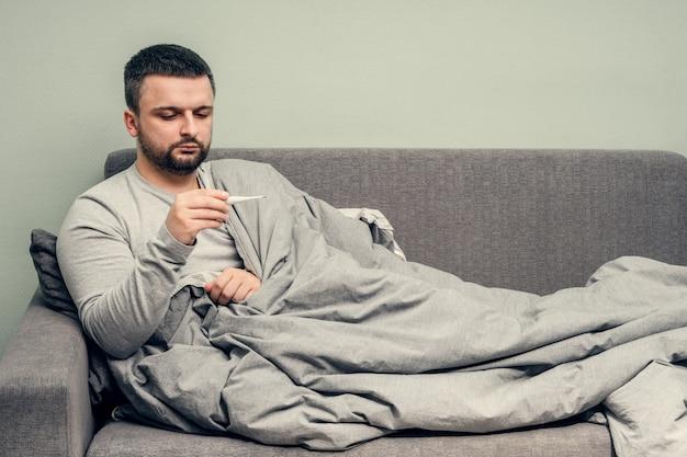Krankheit. zu hause jubeln. ein junger mann ist krank, wird zu hause behandelt. schlägt ihre nase in eine serviette, laufende nase. körpertemperaturmessung. infektion, epidemie, bazillus-träger. coronavirus