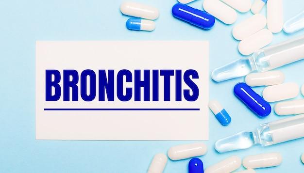 Krankheiten, ampullen und eine weiße karte mit dem text bronchitis auf hellblauem grund. medizinisches konzept