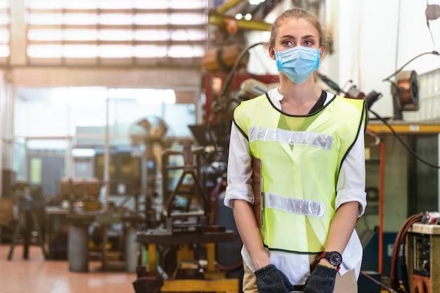 Krankheitsfabrikarbeiterin mit maskenabdeckungsgesicht steht mit dem hintergrund der innenfabrik.