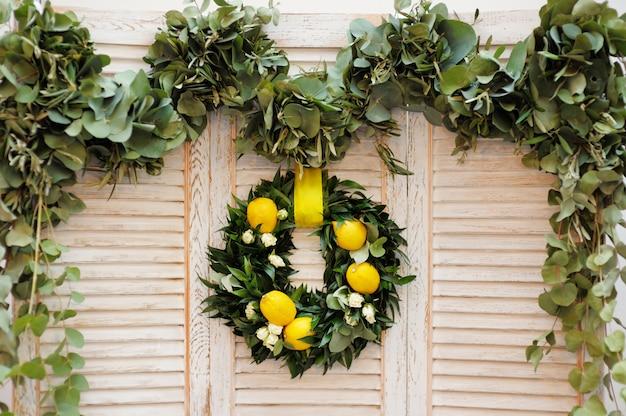 Kranz aus lorbeerblättern, rosen und zitronen als dekoration auf holz