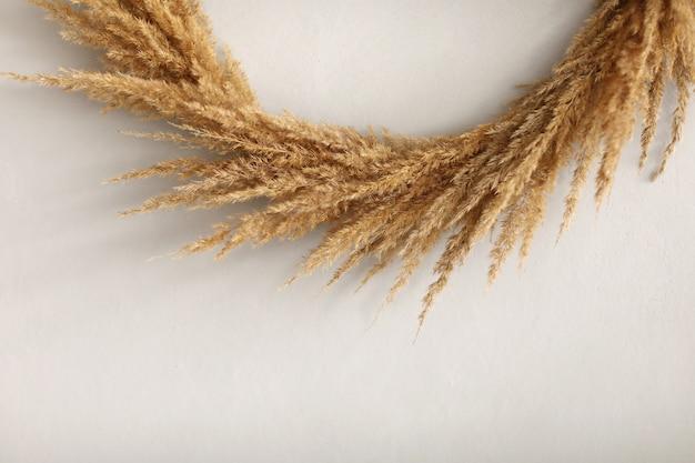 Kranz aus trockenen zweigen isoliert auf weißer wand. weihnachts- oder osterdekor. dekorativer kranz. rahmen aus getrockneten pflanzen und zweig. kranz aus getrockneten kräutern.