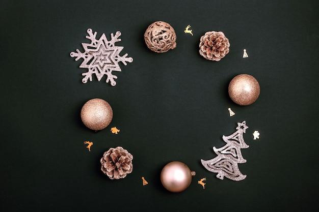 Kranz gemacht von den goldenen weihnachtsdekorationen - glänzende bälle, weihnachtsbaum, kiefernkegel und schneeflocke auf schwarzem papierhintergrund. draufsicht, flache lage, kopienraum