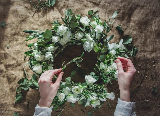 Kranz mit weißen rosen auf jutehintergrund. dekoriert