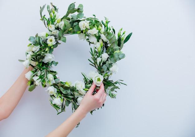 Kranz mit weißen rosen auf weißem hintergrund. dekoriert