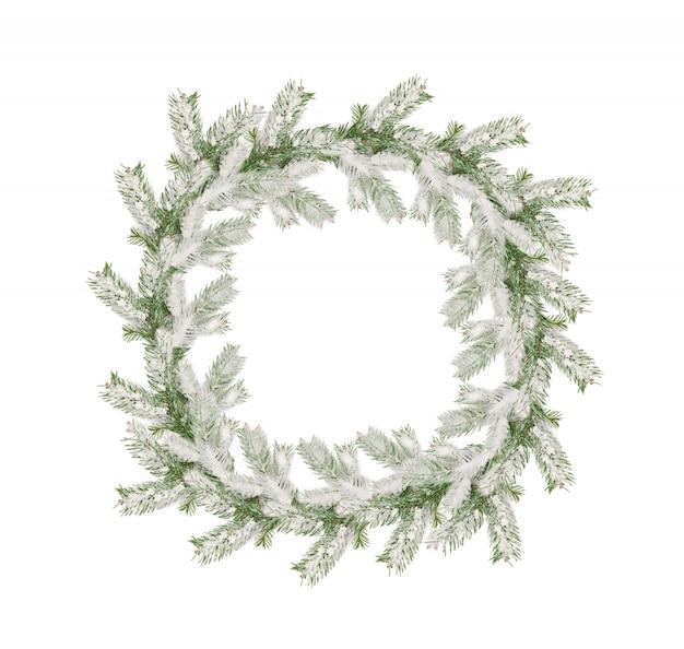 Kranz von den schneebedeckten niederlassungen des weihnachtsbaums lokalisiert auf weiß