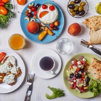 Krapfen zucchini mit tzatziki-sauce, griechischem salat, joghurt mit frischem obst und nüssen, oliven, gemüse und kräutern