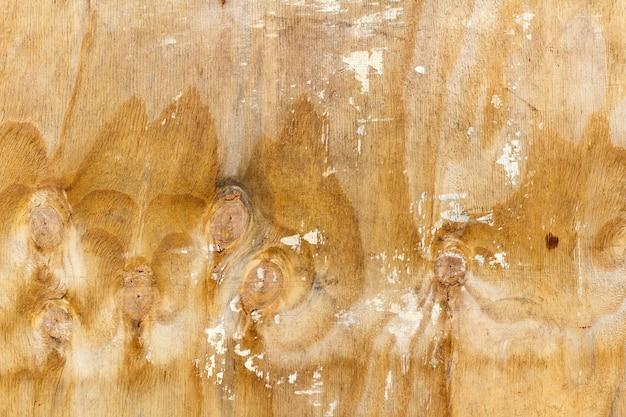 Kratzende oberfläche einer birkensperrholzplatte mit spuren weißer farbe. natürliche holzstruktur. abstrakter hintergrund