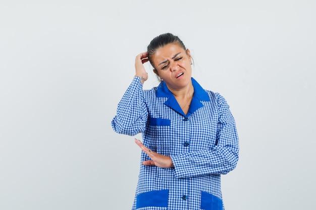 Kratzkopf der jungen frau beim stehen in der denkenden haltung im blauen gingham-pyjamahemd und nachdenklich aussehend. vorderansicht.
