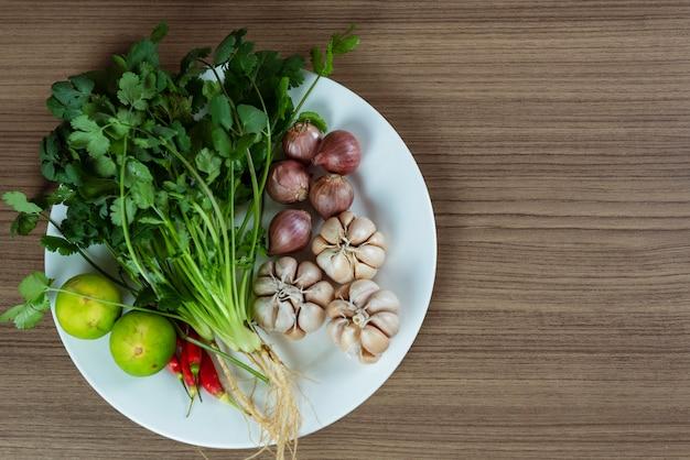 Kraut und bestandteile für würzige thailändische suppe tom yam auf weißer platte