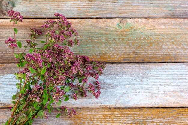 Kraut, zweige des blühenden oreganos auf einem hölzernen weinlesehintergrund mit kopienraum würzend