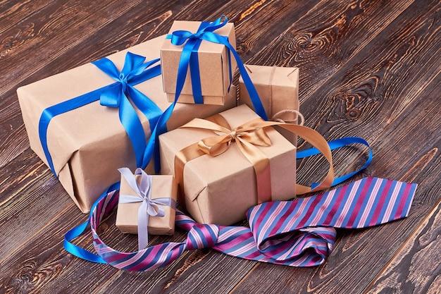 Krawatte in der nähe von geschenkboxen. geschenke auf hölzernem hintergrund. feiertagsgrußtradition.