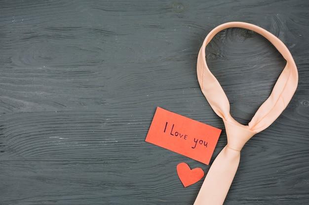 Krawatte in der nähe von papier mit ich liebe dich titel