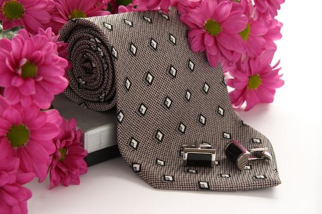 Krawatte und manschettenknöpfe mit blumen über weiß