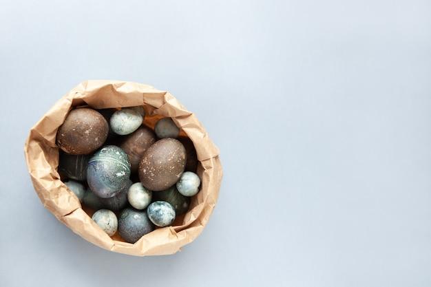 Kreativ bemalte hühner- und wachtel-ostereier mit natürlichem hibiskus-farbstoff sehen aus wie seesteine in der basteltasche auf einem grauen hintergrund. frohe ostern diy-konzept. weicher slective fokus. flach legen, raum kopieren