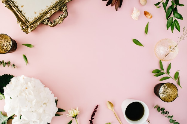 Kreativ dekoriertes und arrangiertes flachrahmenkonzept mit vintage-tablett, hortensie, muscheln, kaffee, goldenem löffel, zweigen auf rosa