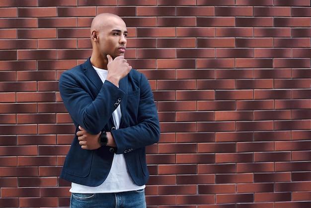 Kreativ denkender junger mann, der nachdenklich an der wand steht