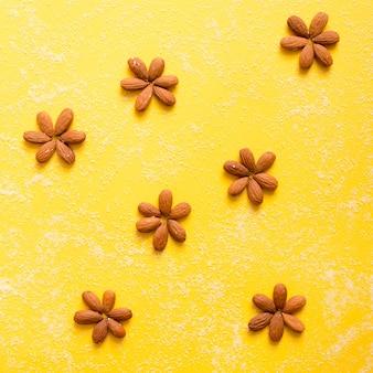 Kreative anordnung der nüsse an der gelben wand. flach liegen.
