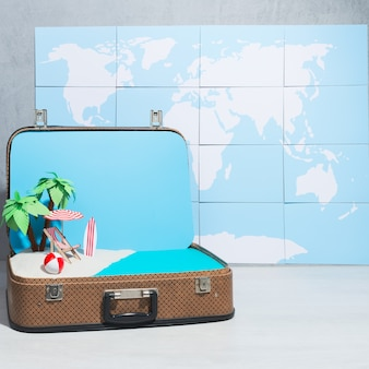 Kreative anordnung des spielzeugstrandlayouts innerhalb des koffers auf hintergrund der weltkarte