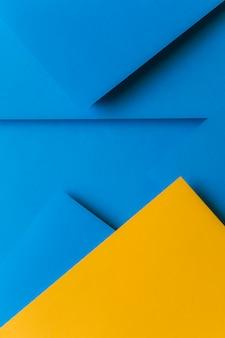 Kreative anordnung für gelbes und blaues farbiges papier, das einen abstrakten hintergrund schafft