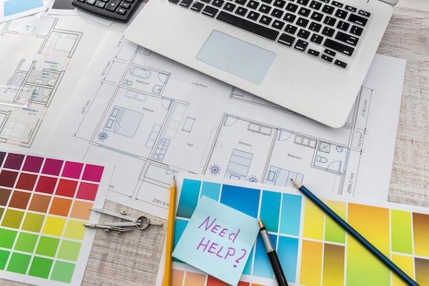 Kreative arbeit am bürolaptop mit hausskizze, taschenrechner und farbmuster. architektenentwurfsprojekt