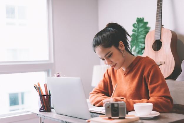 Kreative arbeit der asiatischen jungen frau am laptop-computer am morgen - arbeiten vom hauptkonzept