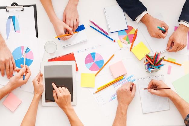 Kreative arbeit. draufsicht auf geschäftsleute, die zusammenarbeiten, während sie am tisch sitzen