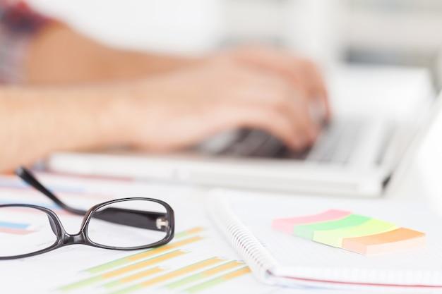 Kreative arbeit leisten. abgeschnittenes bild eines mannes, der am laptop arbeitet, während er an seinem arbeitsplatz sitzt