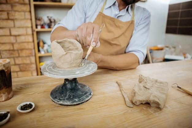 Kreative arbeit. professioneller reifer handwerker, der seine kreative arbeit mit keramik-jigger ausführt
