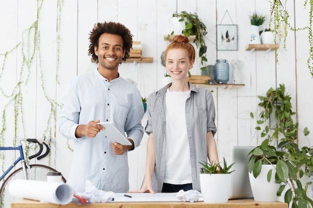 Kreative arbeiter, die in der nähe des arbeitstisches stehen und glücklich sind, ihre arbeit zu beenden