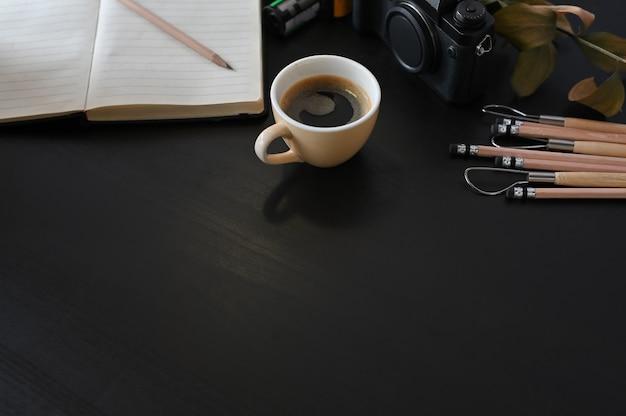 Kreative arbeitsplatzkamera, -kaffee und -briefpapier auf schwarzer tabelle mit selektivem fokus.