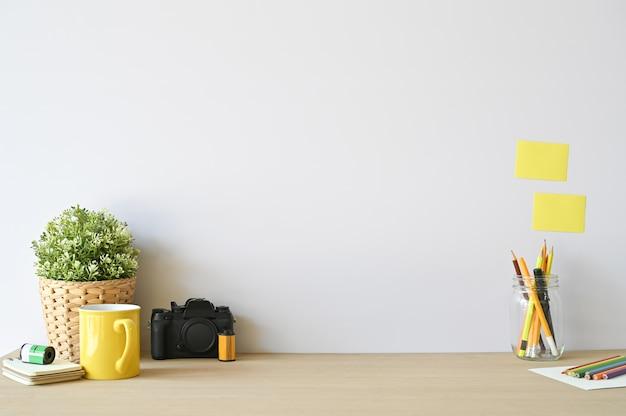 Kreative arbeitsplatzkamera und büroartikel auf hölzernem schreibtisch mit kopienraum.