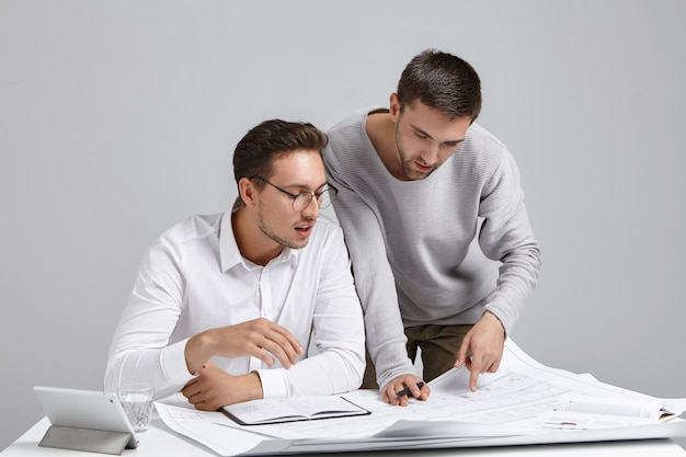 Kreative architekten entwickeln hauspläne, schauen sich baupläne genau an, studieren zeichnungen,