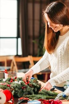Kreative dame, die an der neuen festlichen weihnachtsinnendekoration arbeitet.