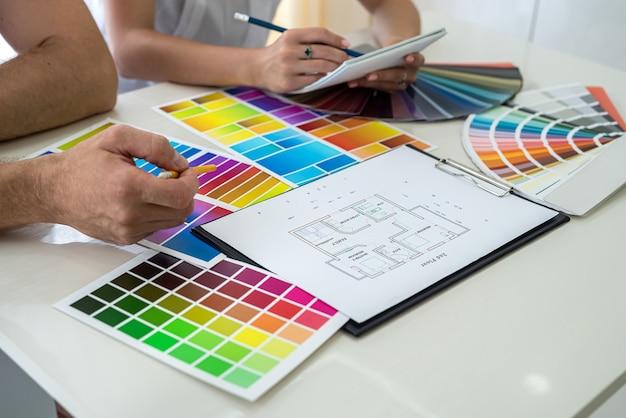 Kreative designer machen sich notizen zu neuen projekten im notizbuch