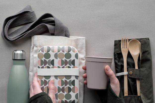 Kreative draufsicht, abfallfreies lunch-konzept, lunchbox zum mitnehmen mit bambusbesteck, wiederverwendbare box, baumwolltasche und hand mit kaffee zum mitnehmen. nachhaltiger lebensstil, flach auf bastelpapier liegen.